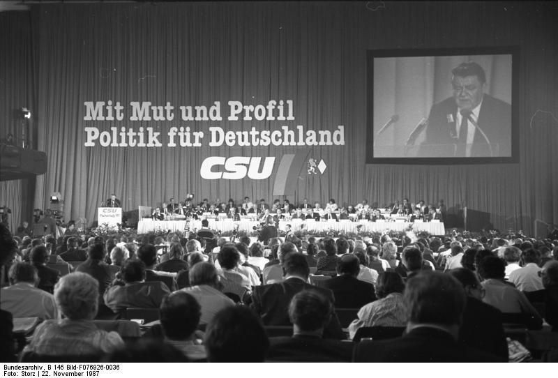 CSU-Parteitag 1987. In einer großen Halle sitzen die Delegierten, auf einer Leinwand hinter der Bühne ist der Vorsitzende Franz Josef Strauß bei seiner Rede zu sehen.