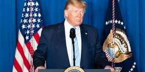 Donald Trump spricht vor der US-Flagge hinter einem Rednerpult, es ist nur der Oberkörper zu sehen.