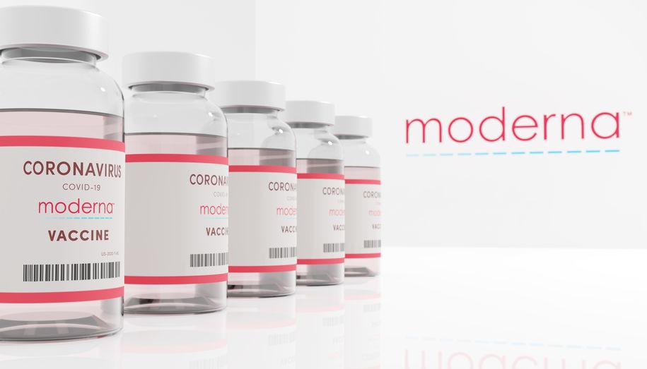 Mehrere Impfdosen von Moderna stehen aufgereiht nebeneinander.