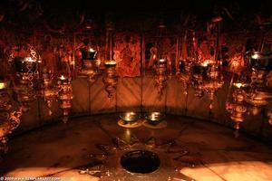Kuhle unter einem Altar in der Geburtskirche mit Leuchtern geschmückt.