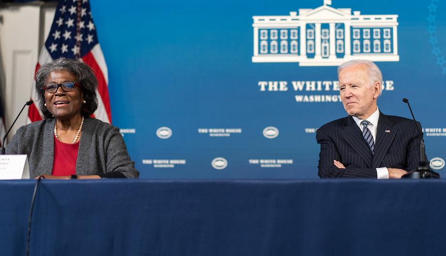 Joe Biden sitzt hinter einem Tisch mit blauer Decke bis zum Boden und schaut zu 2 Meter links von ihm sitzenden schwarzen Frau, die gerade in ein Mikro spricht.