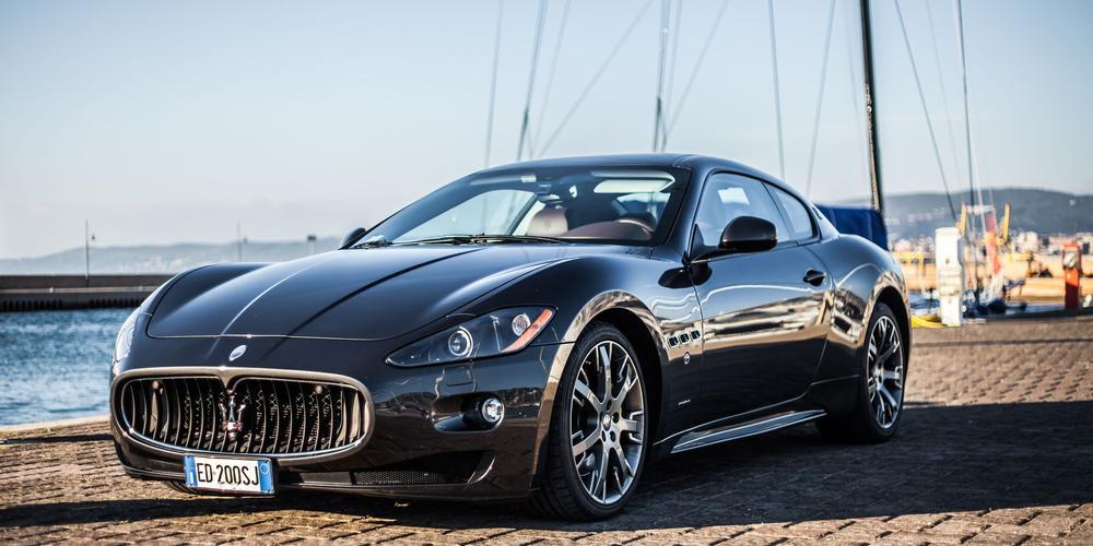 Ein blauer Maserati Granturismo auf einer Hafenpromenade.