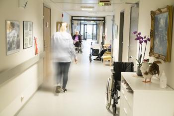 Gang auf einer Pflegestation. Alte sitzen im Rollstuhl, eine Pflegerin eilt entlang.