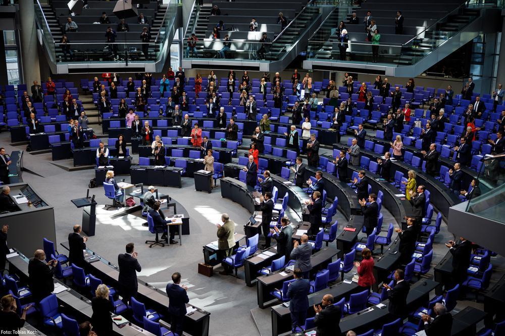 Abgeordnete im Deutschen Bundestag applaudieren. Sie haben viel Abstand voneinander.