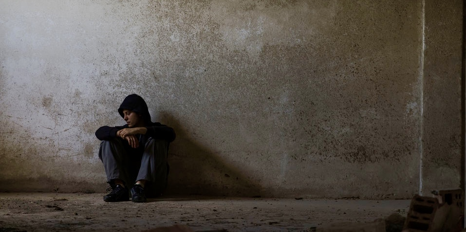 Ein Mann hockt in einem leeren, düsteren Raum vor einer Wand.