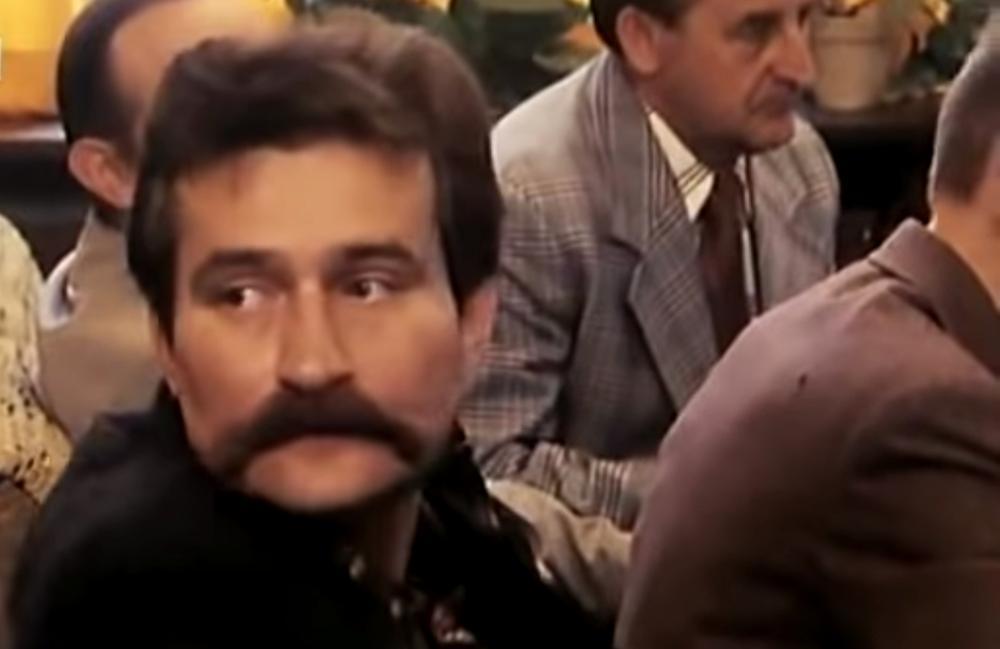 Lech Walesa sitzt mit anderen in einer Versammlung und blickt zur Seite.