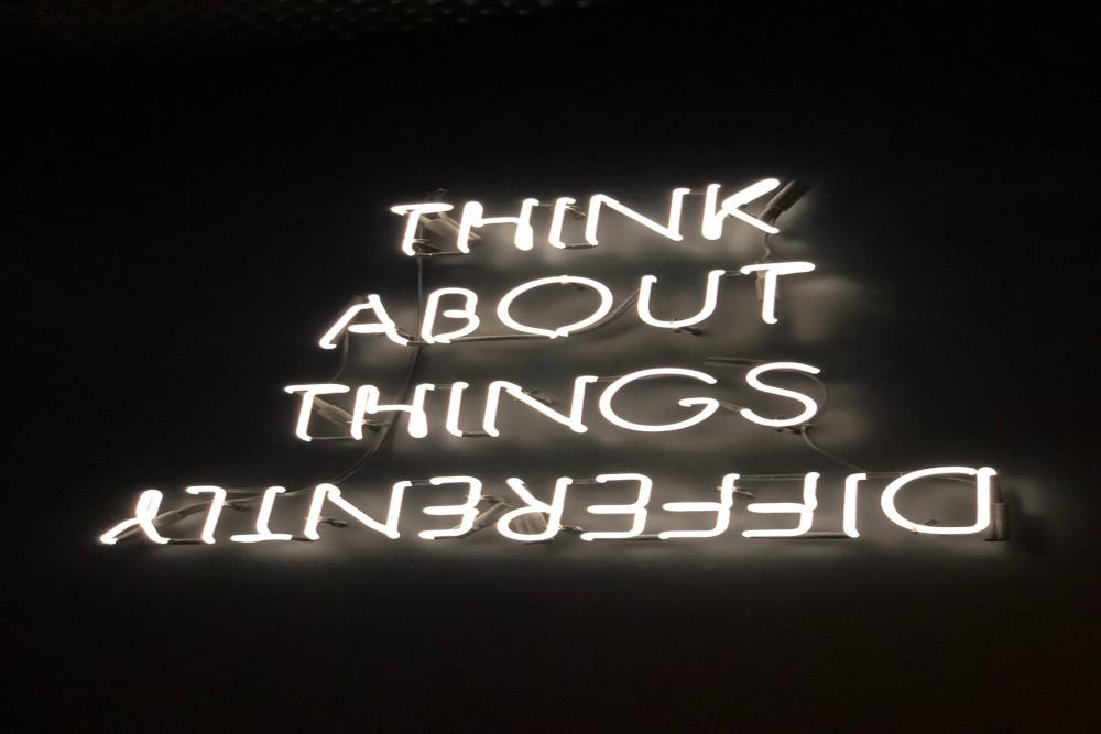 Neonschriftzug, in jeder Zeile ein Wort: Think About Things Differently. Das letzte Wort steht auf dem Kopf.