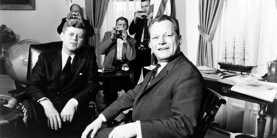 Willy Brandt sitzt mit John F. Kennedy im Oval Office des Weißen Hauses, im Hintergrund stehen Fotografen. Die Aufnahme ist in Schwarz-Weiß.