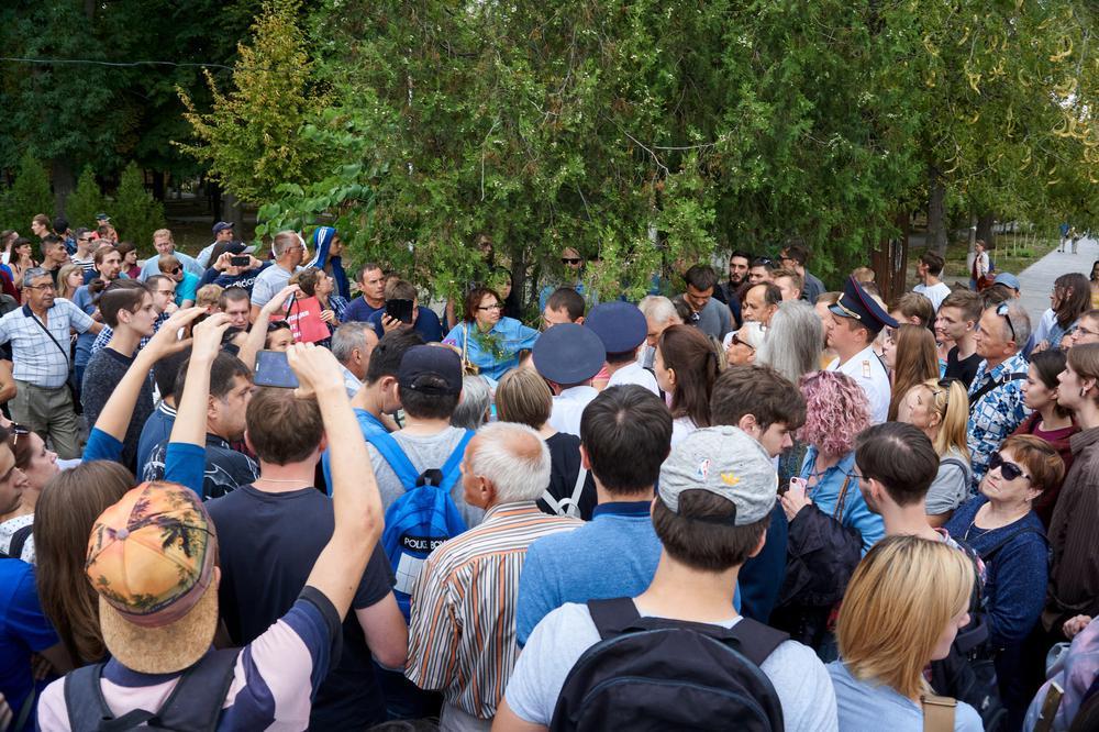 Protestierende haben sich am Rande eines Parks versammelt.