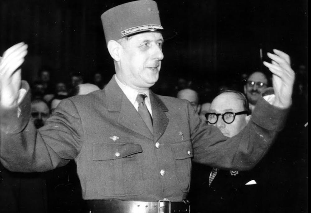 Charles de Gaulle in Miltiäruniform steht mit ausgebreiteten Armen, leicht nach oben gebeugt, da. Hinter ihm im Dunkeln sind einige Menschen zu erkennen.