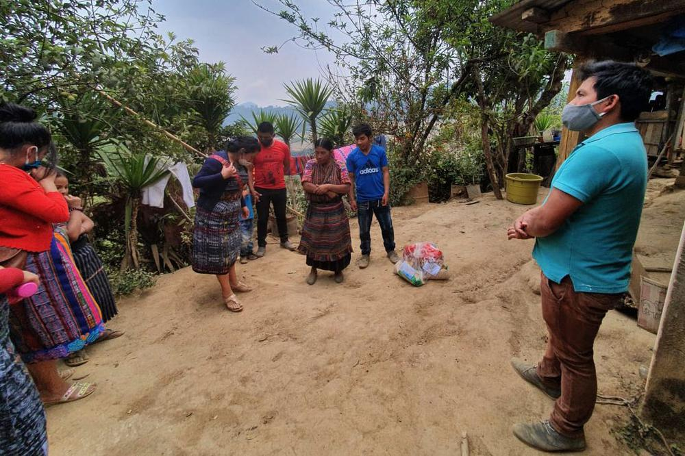 Dorfbewohner stehen im Kreis auf erdigem Boden, die meisten mit Gesichtsmasken.