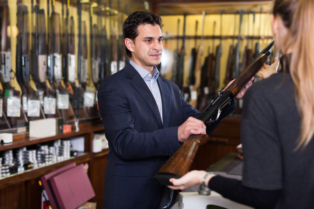 In einem Waffengeschäft zeigt ein grimmig blickender Verkäufer einer Frau, die mit dem Rücken zur Kamera steht, ein Gewehr.