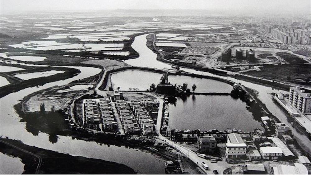 Schwarzweißbild von einer Landschaft mit einem mändernden Fluss und einer Stadt auf der rechten Seite und auf einer Halbinsel im unteren Teil des Bildes..