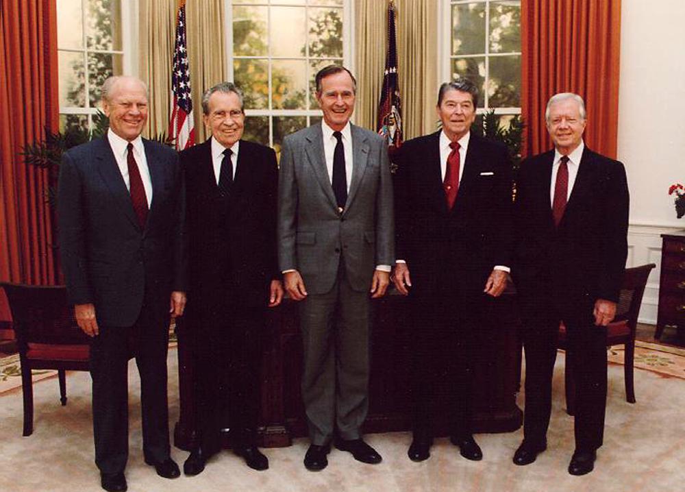 Fünf Männer stehen in dunklen Anzügen ebeneinander im Oval Office, dem Büro des US-Präsidenten: Gerald Ford, Richard Nixon, George W. Bush, Ronald Reagen, Jimmy Carter.
