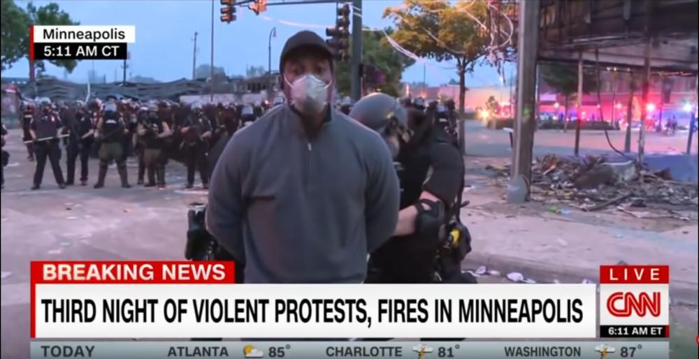 Zwei weiße Polizisten legen einem dunkelhäutigem Reporter vor seinem Kamerateam Handschellen hinter dem Rücken an.