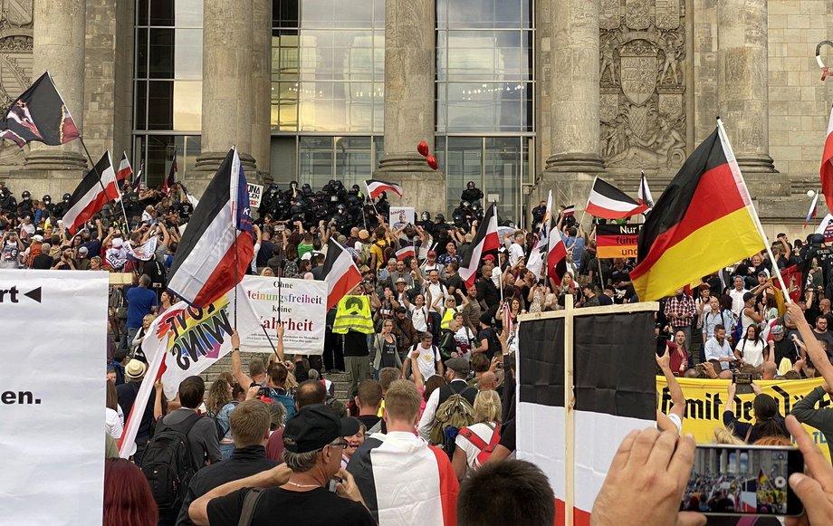 Protestierende stehen auf den Stufen vor dem Reichstagsgebäude. Einige schwenken Reichsflaggen, andere schwenken Transparente, die Meinungsfreiheit verlangen.