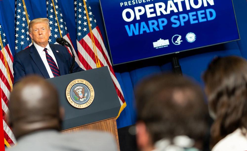 Donald Trump steht auf einem Podium hinter einem Rednerpult, im Hintergrund US-Flaggen und rechts eine Tafel, auf der steht: Operation Warp Speed.