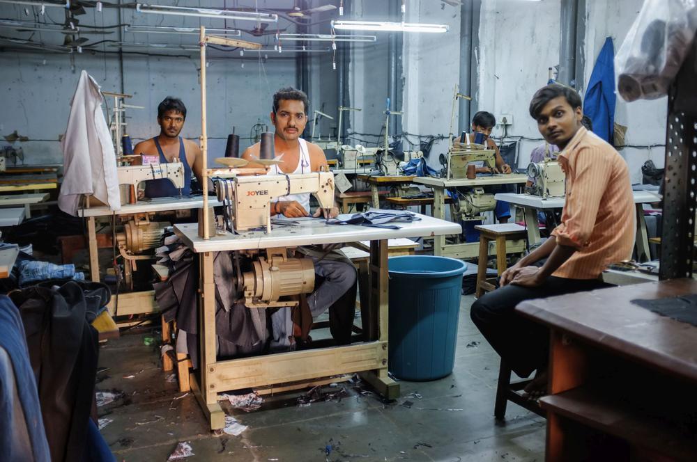 Näher in einer indischen Fabrik sitzen aufgereiht hintereinander an Nähmaschinen und blicken in die Kamera.