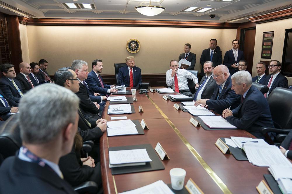 Rund um einen langen Tisch sitzen Trump und viele weiße Männer.