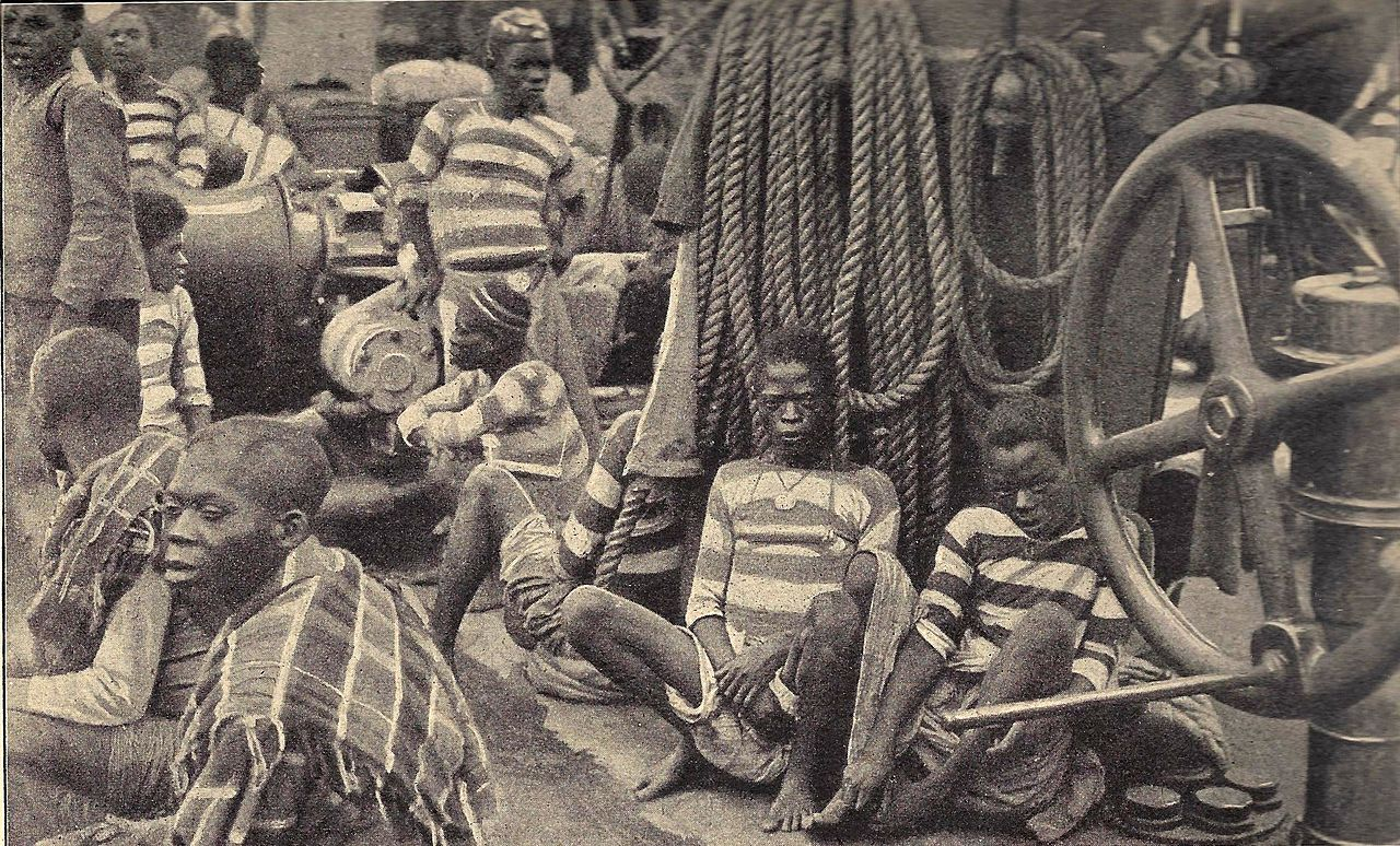 Schwarzweiß-Bild von dunkelhäutigen angeketteten Sklaven in Sträflingskleidung auf einem Schiff.