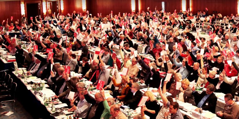 Blick in eine Messehalle mit aufgereihten Tischen, an denen Delegierte sitzen. Der Stühle sind bis auf den letzten Platz besetzt