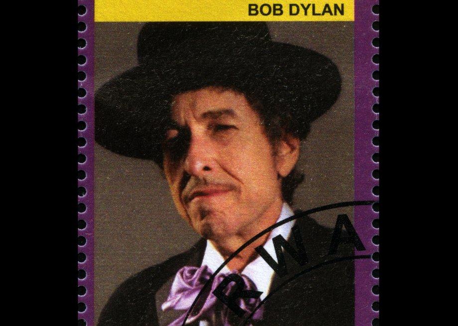 Briefmarke aus Ruanda mit dem Portrait von Bob Dylan. Er trägt einen schwarzen Hut, ein schwarzes Jackett und eine große lila Fliege über einem weißen Hemd.
