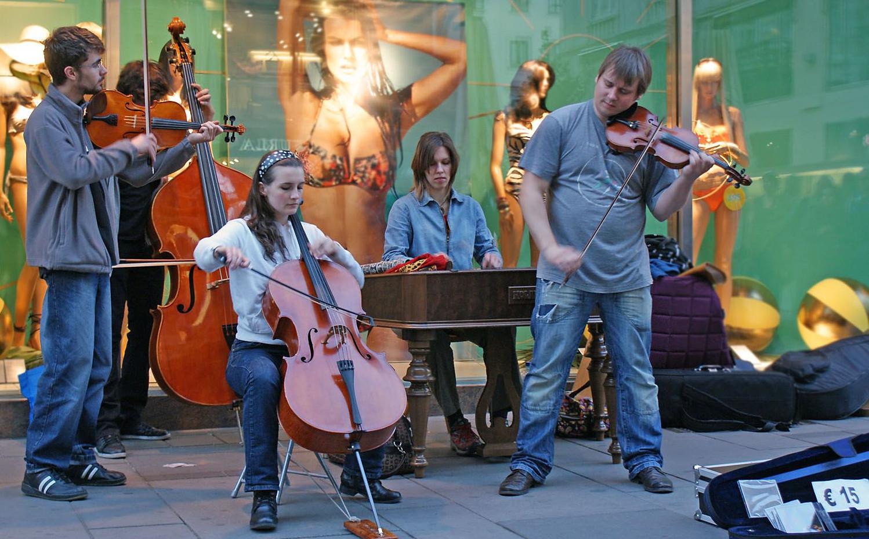 Straßenmusiker - mit Bass, Viola, Violine, Cello und Cembalo - spielen vor einem Schaufenster, rechts liegt der Cellokasten offen für Spenden und eine CD darauf, die für 15 Euro angeboten wird.