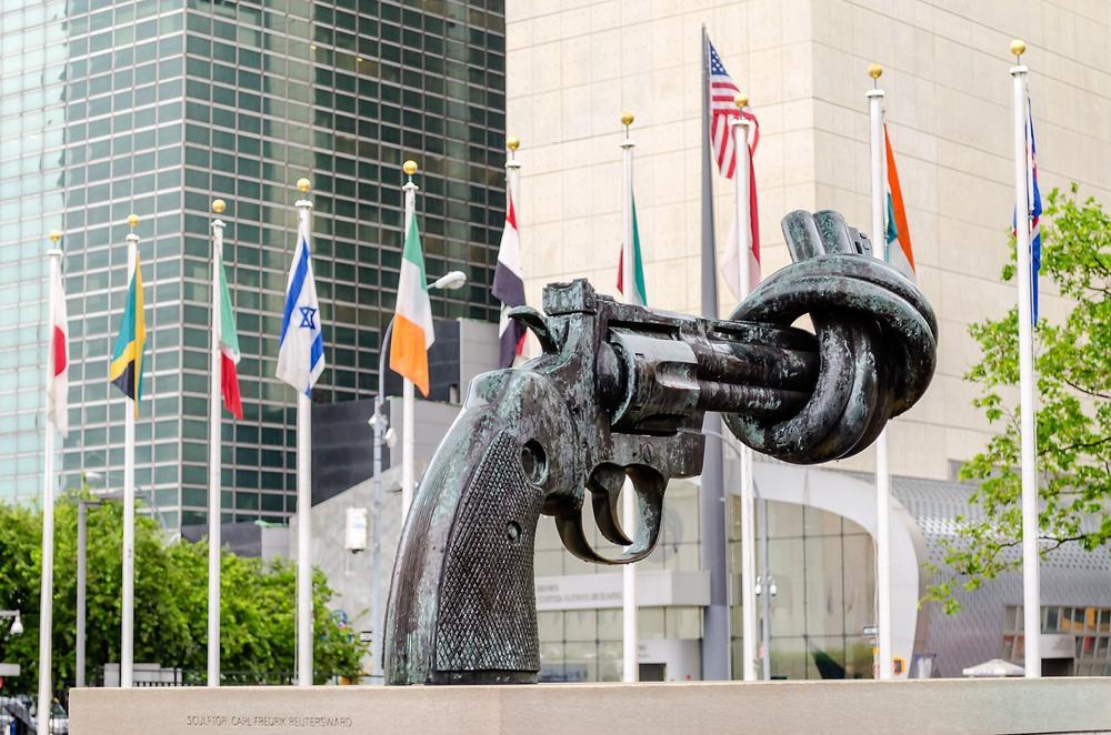 Flaggen und die Skulptur eines verknoteten Revolvers, als Zeichen gegen Gewalt, stehen vor dem Gebäude der Vereinten Nationen in New York.