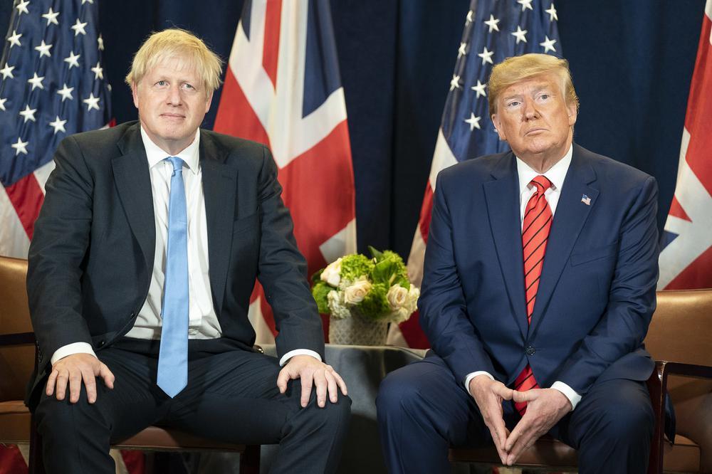 Boris Johnson und Donald Trump sitzen nebeneinander vor britischen und amerikanischen Flaggen.