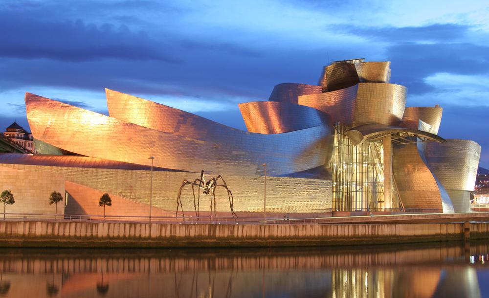 Die golden schimmernde geschwungene Fassade des Guggenheim-Museums in Bilbao von der anderen Seite des Flusses aufgenommen.