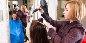Ein Friseurin fönt einer Kundin, die vor ihr sitzt die Haare.