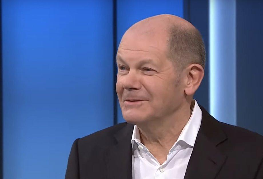 Olaf Scholz steht vor einer blauen leuchtenden Wand in einem TV-Studio und lächelt. Sein Blick ist zur linken Seite gerichtet.