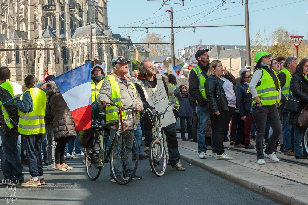 Protestierende in Gelbwesten marschieren eine Straße entlang