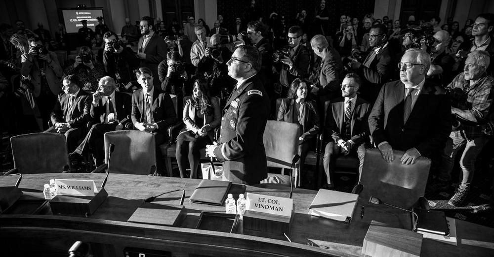Oberstleutnant Alexander Vindman steht hinter einem Tisch in einem Raum des US-Repräsentantenhauses und wartet auf seine Aussage, währenddesen fotografieren ihn Fotografen.