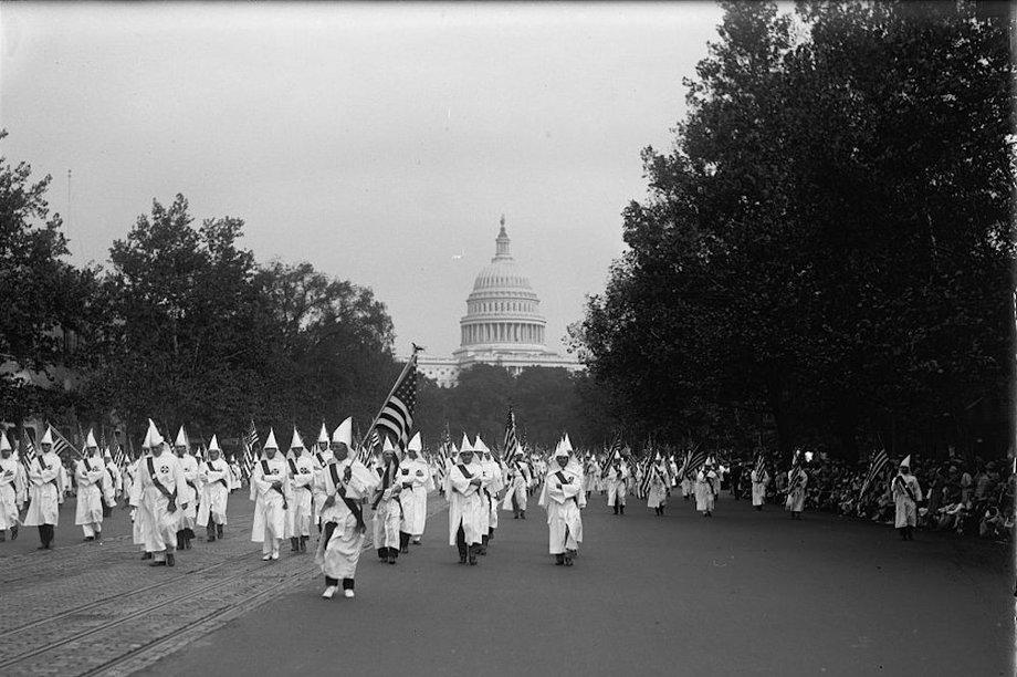 Schwarzweißbild von Männern mit weißen Gewändern und Kapuzen, die vom Kapitol, das im Hintergrund zu sehen ist. in einer Parade weg marschieren.