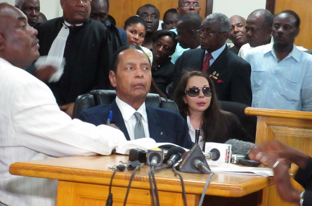 Jean Claude Duvallier sitzt in einem Stuhl vor einem Holztisch. Hinter ihm stehen viele Menschen dicht gedrängt.