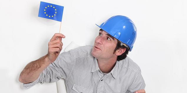 Arbeiter mit Blick auf EU-Flagge