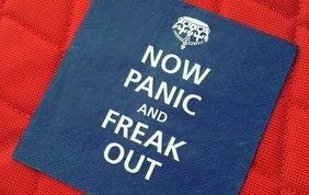 Blauer Aufnäher auf rotem Stoff, auf dem steht: Now panic and freak out.