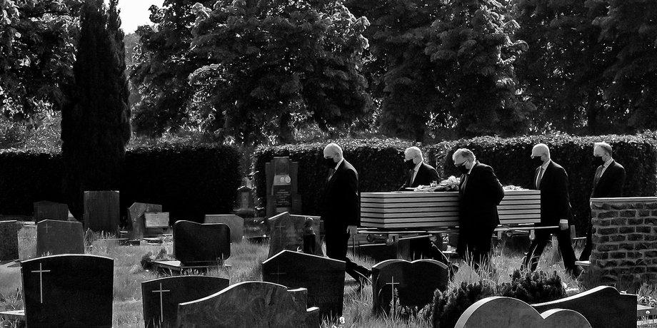 Auf einem Friedhof tragen vier Männer in schwarzen Anzügen und schwarzen Gesichtsmasken einen schlichten Holzsarg zu einem Grab. Bild in Schwarzweiß.