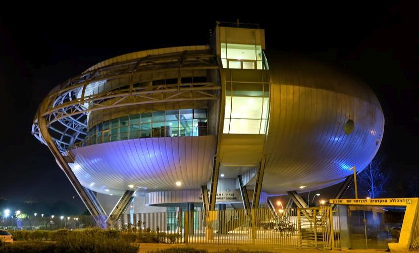 Technische Hochschule Beer Sheva: Ein rundes Gebäude mit metallen wirkender Phase bei Nacht, das ein wenig wie ein Ufo aussieht.