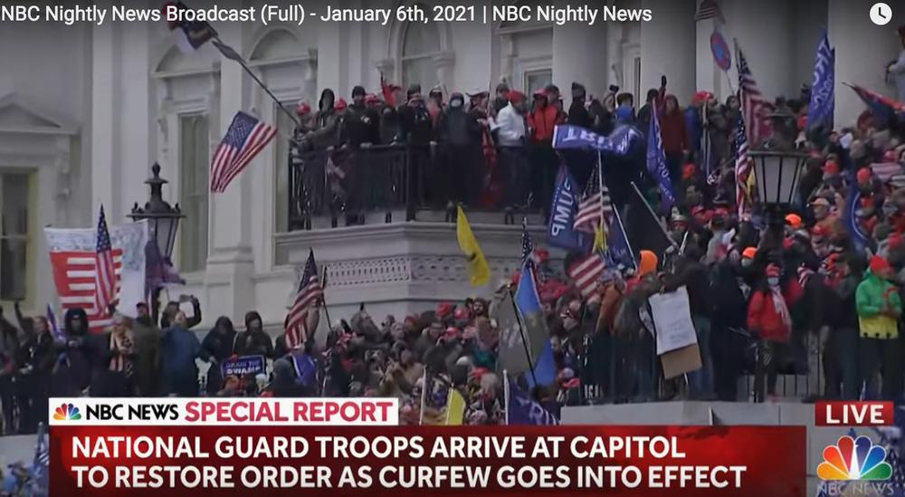 Protestierende Menschen auf den Stufen des Kapitols mit US-Flaggen und Trump-Flaggen.