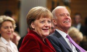 Joe Biden sitzt neben Angela Merkel, er im blauen Anzug, sie trägt einen roten Blazer. Dahinter unscharf, aber zu erkennen Ursula von der Leyen.