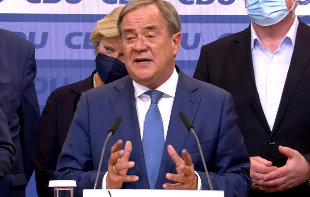Ein Mann steht hinter einem Rednerpult und spricht mit etwas grimmiger Miene.