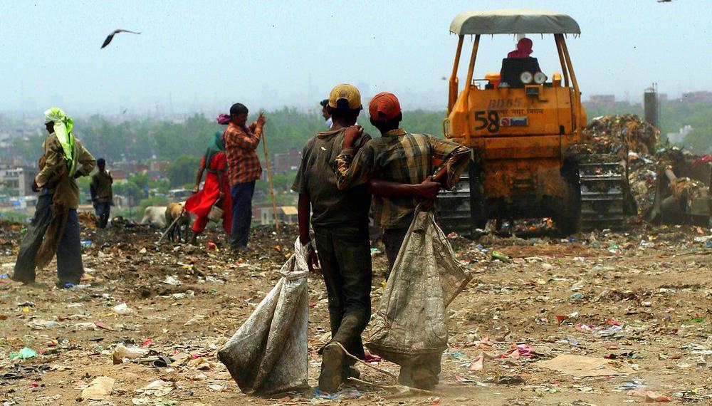 Müllsammler auf einer Halde, von hinten aufgenommen, gehen auf einen Bagger im Hintergrund zu.
