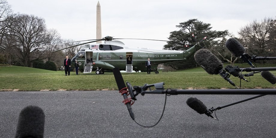 Mikrophone im Vordergrund, im Hintergrund der Hubschrauber Marine One, vor dem Donald Trump steht.