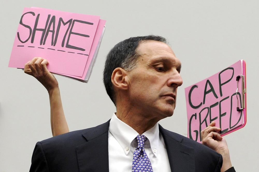 Der Vorstandsvorzitzende von Lehman Brothers, Richard Fuld, steht im Kongress bei einer Anhörung, hinter ihm Protestschilder, die ihm Gier vorwerfen.