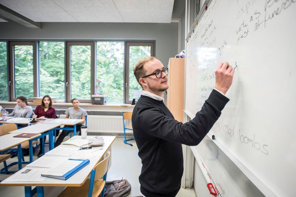 Ein Lehrer schreibt an einer Tafel und erklärt, während im Hintergrund Schüler aufmerksam zuhören.