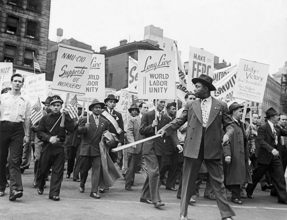 """Schwarze Demonstratenten halten wie """"Long live Labor Unity"""" hoch. Das Bild ist in Schwarzweiß."""