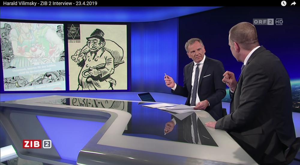 ORF-Moderator Armin Wolf befragt im TV-Studio den FPÖ-Generalsekretär Harald Vilimsky zu einer rassistischen Grafik der FPÖ-Jugend, die im Hintergrund zu sehen ist. Darauf großnasig, fremdartig aussehende Menschen.