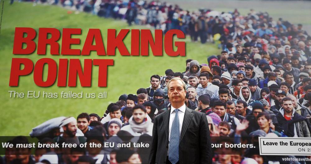 """Der britische Politiker Nigel Farage von der rechten Ukip steht vor einem großen Plakat mit einer Schlange von fremd aussehenden Menschen, auf dem steht: """"We must break free of the EU """""""